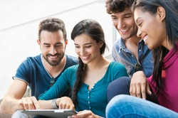 Closeup shot of young men and women looking at digital tablet. Happy smiling group of friends sitting outdoor using digital tablet.   Happy young woman pointing on a digital tablet.