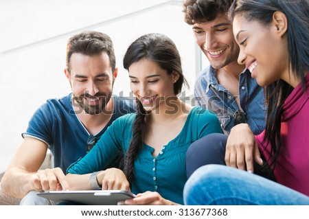 Closeup shot of young men and women looking at digital tablet. Happy smiling group of friends sitting outdoor using digital tablet. \  Happy young woman pointing on a digital tablet.