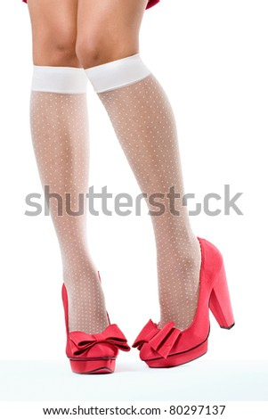 Closeup shot of young woman's legs in fashionable high heel red shoes and white stockings, on white