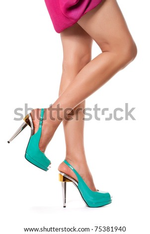 Closeup shot of young woman's legs in fashionable high heel turquoise shoes, on white