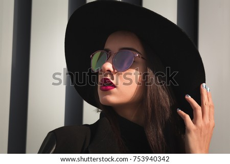 Closeup shot of young woman with bright makeup and shiny hair wears hat and sunglasses