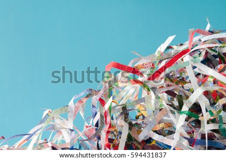 Closeup shredded paper texture and reuse colorful paper scrap of document on blue paper background. Selective focus image.