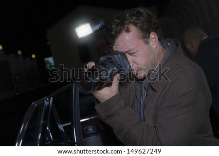 Closeup side view of a photographer at media event