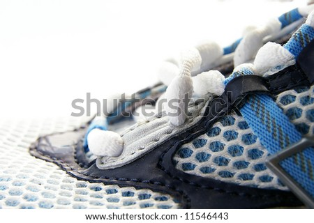 Closeup side view of a running shoe, on white