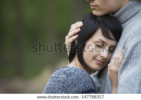 Closeup side view of a young woman laying head on man\'s chest against blurred background