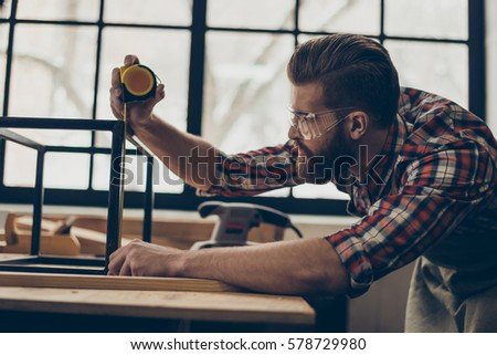 Closeup side view photo of handsome  worker with ruler. Stylish young entrepreneur with brutal hairstyle and saved glasses work at his workplace. He love his job.