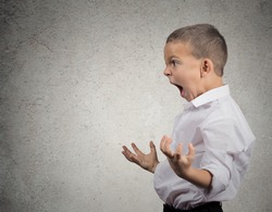 Closeup side view Portrait Angry Child Screaming fists up in air isolated grey wall background. Negative Human face Expression Emotion Reaction Perception. body language Conflict confrontation concept