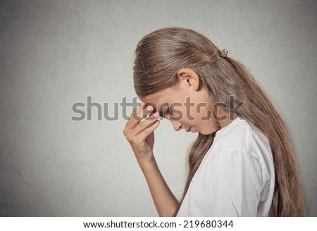 Closeup side view portrait sad tired disappointed teenager girl face on hand looking down isolated grey wall background. Negative human emotion facial expression feeling life perception body language