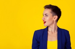 Closeup side view profile portrait head shot woman talking singing invisible sound coming out of her open mouth isolated on yellow background with copy space. Model in yellow shirt and blue suit.