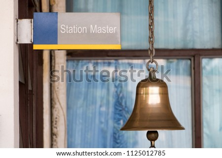 Closeup sign station master with a golden bell in train station. Traditional sound signaling on the platform at the railway station.  #1125012785