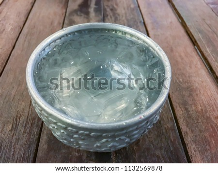 Closeup silver bowl of ice and pure water on old wooden table, traditional or cultural cool water drinking of Thai rural folks lifestyle, help refreshing or relief thirsty