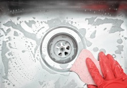 Closeup sink drain and hand wearing organge rubber glove cleaning scrub steel sink with sponge. Housework concept