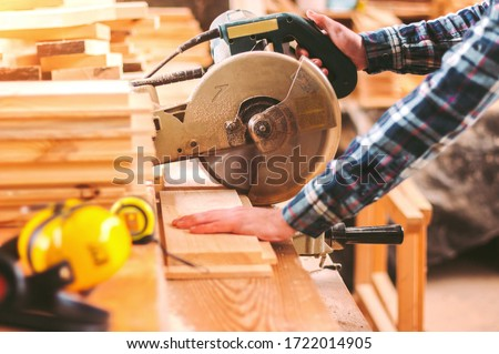 Closeup skilled cabinet maker cutting wood board with electric circular saw at woodworking sawmill. Professional cabinet maker use circular saw at sawmill factory. Wooden furniture production. Joinery