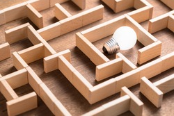 Closeup small light bulb in the maze game built by wood blocks, finding the right way to the success, searching creative idea concept