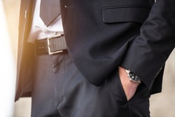 closeup smart businessman hand at pocket waiting with watch in nice black suit sun outdoor