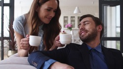 Closeup smiling couple drinking tea at home together. Happy woman bringing cups of tea for husband in living room. Portrait of joyful couple taking coffee break on sofa in slow motion.