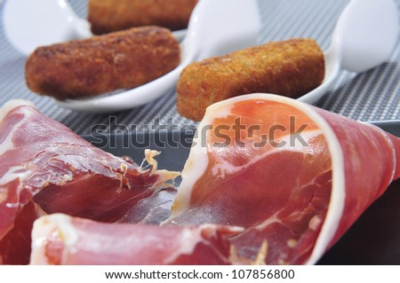 closeup some plates with spanish croquettes and serrano ham served as tapas - stock photo