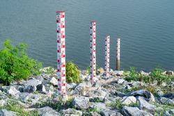 Closeup staff gauge water at dam background. Four red water level gauge scale at lake