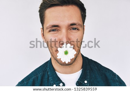 Closeup studio image of Caucasian handsome man smiling with a flower in mouth posing over white wall. Attractive male with a bunch of flowers preparing for a date with his girlfriend.