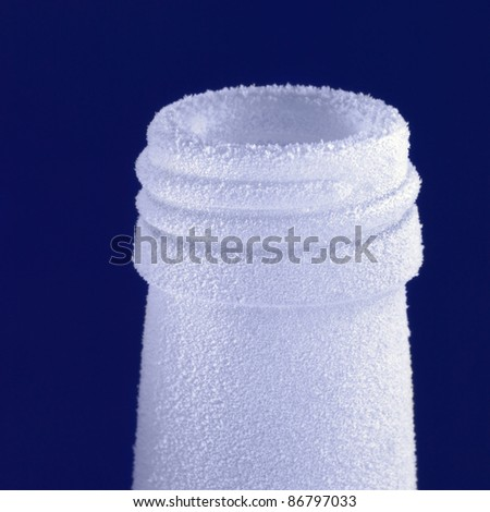 closeup studio photography of a of a frosted bottle in dark blue back