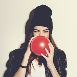 Closeup studio portrait of beautiful trendy hipster teenage girl blowing a red balloon wearing black leather jacket and black beanie hat. Square format, instagram look filter.