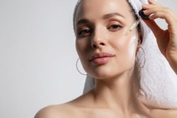 Closeup studio portrait with young woman in bath towel on head isolated on copy space applying oil serum from pipette. Natural organic cosmetic product for facial skincare and skin regeneration