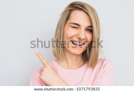 Closeup studio shot of happy blonde female wears pink sweater indicates with fore finger aside, blink with eye, demonstrates something at blank copy space for advertisement. People and emotion concept