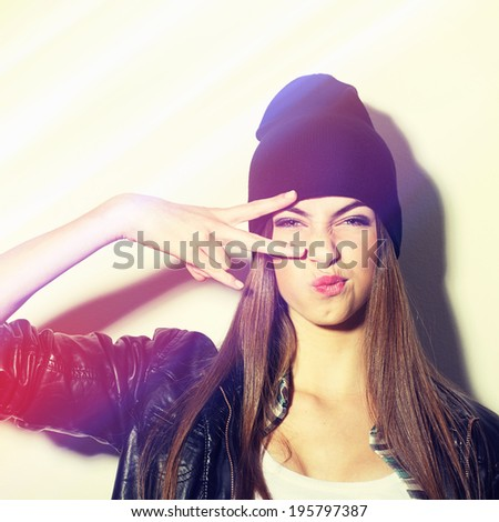 Closeup studio shot of pretty hipster teenage girl with beanie hat pouting gesturing peace. Square image with instant filter applied.