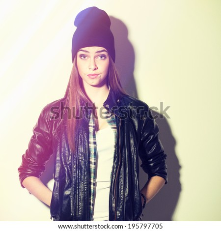 Closeup studio shot of pretty hipster teenage girl with beanie hat wearing black leather jacket looking at camera posing Square image with instant filter applied