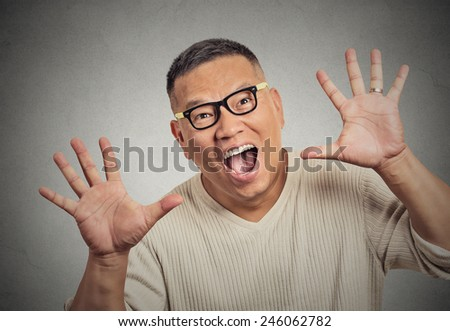closeup super excited funky guy with glasses looking at you arms hands raised at camera isolated grey wall background