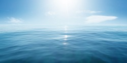 Closeup surface of calm ocean blue sea water with sunshine and clouds behind. Abstract Background Texture.