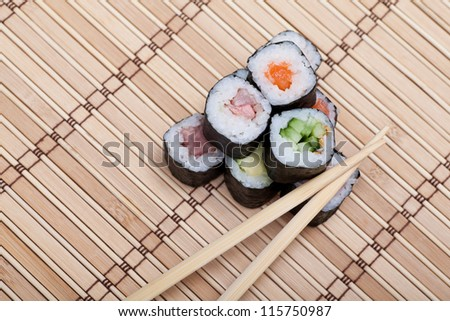 closeup sushi and chopsticks on bamboo mat. top view