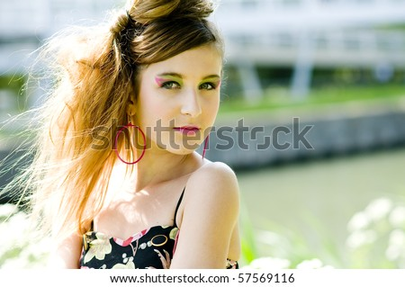 Closeup teenage girl model presenting clothes in the park near the water and a bridge