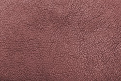 Closeup textured red leather textile material surface. For cracked texture pattern