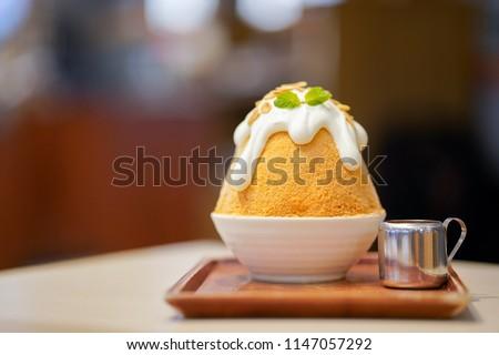 Closeup thai milk tea Bingsu on tray, Bingsu or Bingsoo, Korean shaved ice dessert with sweet toppings and fruit and varieties with ingredients, popular dessert, using as a background or wallpaper