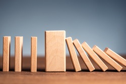Closeup thick domino wood block in a row stop the falling, be stable in crisis, business solution concept