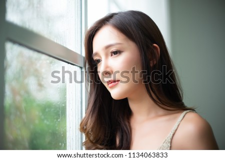 Closeup Thoughtful young Asian woman looking through glass window with raindrops at her home. Autumn melancholy concept