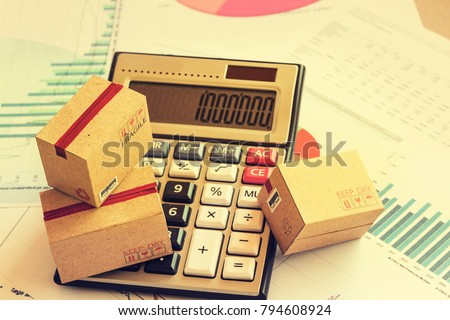 Closeup three cardboard boxes packing the product and calculator on technical chart of financial expansion. Idea of marketing planning and shipping costs, Control financial budget and service charge. Stock foto ©
