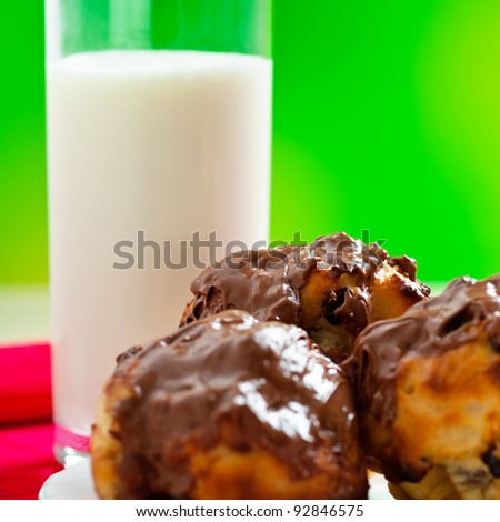 closeup three cupcake decorated with chocolate with raisins in white plate, glass of milk background outdoors,wooden table