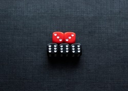 Closeup to a black and red dices. three black dices and two red dices over black background. Ideal for gamble, board games and bets