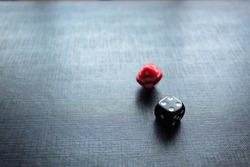 Closeup to a dices, one dice is black and one dice is spinning over a black background. Ideal fo gamble, board games and bets