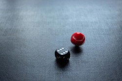 Closeup to a dices, one dice is red and one black dice is spinning over a black background. Ideal for gamble, board games and bets