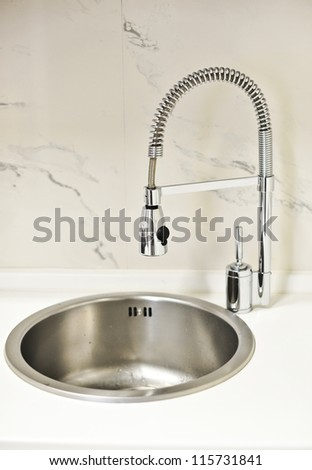 closeup to a modern stainless steel kitchen sink .designer kitchen sink with chrome water tap