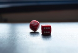 Closeup to a red dices, one dice is spinning over a black background. Ideal fo gamble, board games and bets
