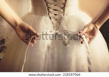 Closeup toned photo of beautiful bride tying up her wedding dress Foto stock ©