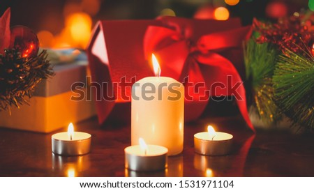 Closeup toned photo of burning candles against lots of colorful boxes with Christmas gifts and presents