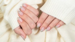 Closeup top view of beautiful natural look trendy manicure of  French nail design. Pink nails with glossy silver isolated on pastel white knitte background. Winter or autumn style of nail design.