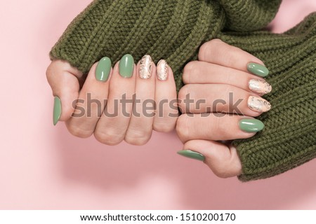 Closeup top view of beautiful two faded colors trendy manicure of  green and pink nails with glossy silver stamp design isolated on pastel pink background. Winter or autumn style of nail design concep