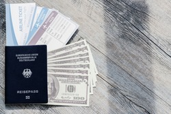 Closeup top view shot of dark blue German Deutschland passport one hundred US dollar unfold banknotes cash heap and airline flight ticket boarding pass arrival and departure on old wood texture desk.