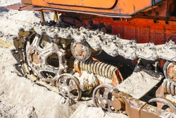 closeup tracked bulldozer drive mechanism that stands on the sandy beach